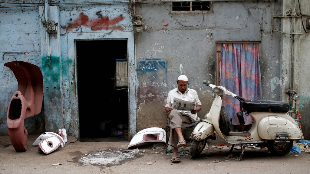 """Amin, who paints repaired Vespa scooter parts, reads a newspaper outside his workshop in Karachi, Pakistan February 28, 2018. REUTERS/Akhtar Soomro  SEARCH """"VESPA PAKISTAN"""" FOR THIS STORY. SEARCH """"WIDER IMAGE"""" FOR ALL STORIES. TPX IMAGES OF THE DAY."""
