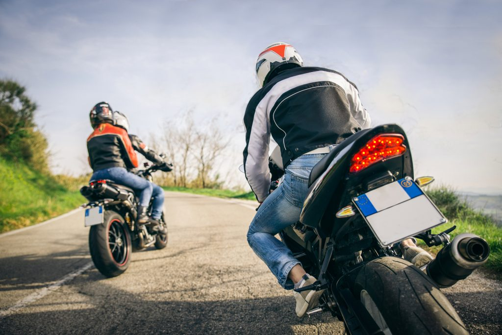 Two motorbikes driving in the nature - Friends driving racing motorcycles with their girlfriends